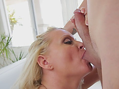 A slutty blonde mommy works on horny young stud's hard penis passionately